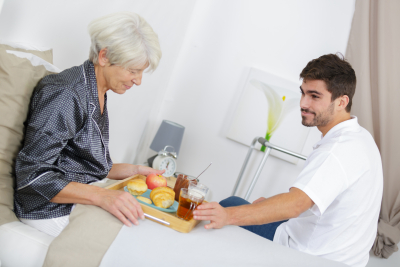 caregiver serving breakfast in bed to senior woman
