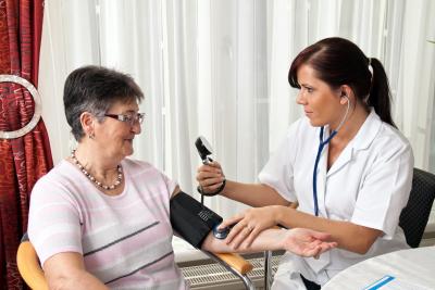 nruse measuring patient blood pressure