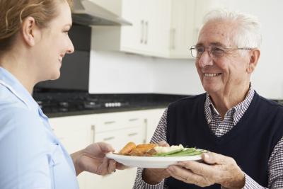 caregiver serving food to senior man