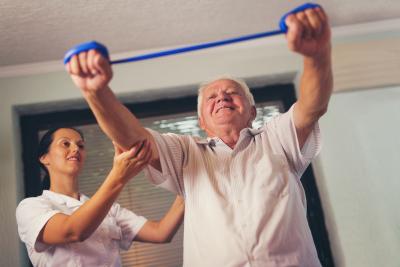 caregiver guiding senior men doing exercise