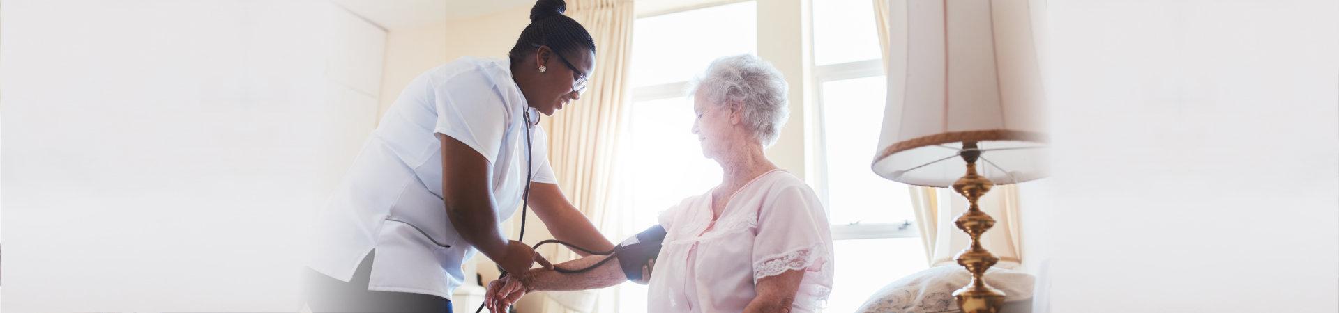 nurse doing blood pressure measurement of a senior woman patient